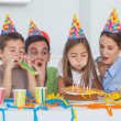 Little girl blowing her candles during her birthday party — Stock Photo #28059143