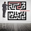 Businessman standing on a ladder drawing line through qr code — Stock Photo