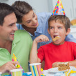 Little boy eating a birthday cake with parents — Stock Photo #28059279
