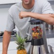 Attractive man leaning on his blender — Stock Photo