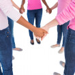 Stock Photo: Women wearing pink and ribbons for breast cancer holding hands i