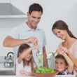 Stock Photo: Family mixing salad together
