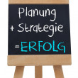 Planning strategy written on blackboard in german — Stock Photo