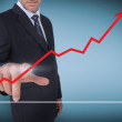 Businessman selecting a red arrow pointing up on a chart — Stock Photo