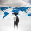 Businessman with an umbrella looking at a world map — Stock Photo #28059681