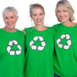 Three women wearing green recycling tshirts smiling at camera — Stock Photo