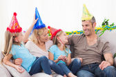 Family celebrating twins birthday sitting on a couch — Stock Photo
