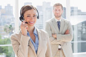 Happy call centre agent with colleague behind her — Stock Photo