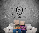 Employees sat on a couch with a light bulb drawing — Stock Photo
