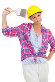 Beautiful handy woman holding a brush and smiling at camera — Stock Photo