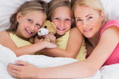 Woman napping in bed with her cute children — Stock Photo