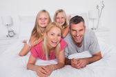 Portrait of parents lying in bed with their twins — Stock Photo
