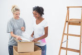 Young housemates unpacking moving boxes — Stock Photo