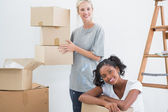 Pretty housemates carrying cardboard moving boxes — Stock Photo