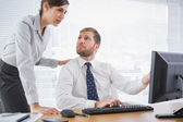 Businessman showing his co worker something on computer — Stock Photo