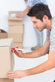 Man writing on a moving box — Stock Photo