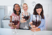 Cheerful friends toasting to the camera with glasses of red wine — Stock Photo