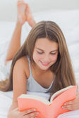 Smiling girl reading a book — Stock Photo
