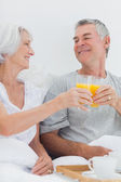 Couple clinking their orange juice glasses — Stock Photo