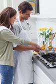 Delighted couple cooking — Stock Photo