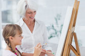 Cheerful grandmother and granddaughter painting together — Foto Stock