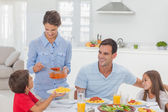 Woman giving pasta sauce to her son — Stock Photo