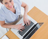 Pretty businesswoman typing on her laptop and smiling up at came — Stock Photo