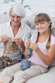 Portrait of a little girl and her granddaughter knitting togethe — Stock Photo