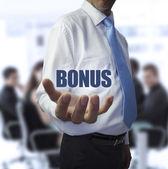 Smart businessman holding the word bonus — Stock Photo