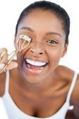 Smiling woman using curler for her eyelash — Stock Photo
