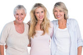 Three generations of happy women smiling at camera — Stock Photo