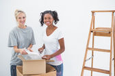 Happy housemates unpacking moving boxes — Stock Photo