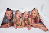 Family playing under the quilt — Stock Photo