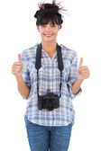 Woman with camera showing thumbs up — Stock Photo