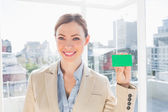 Smiling businesswoman showing green business card — Stock Photo