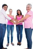 Heureux femmes portant des rubans de cancer du sein mettre ensemble les mains — Photo