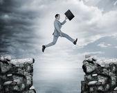 Homme d'affaires sautant un fossé entre les falaises — Photo