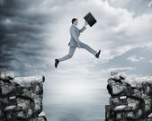 Uomo d'affari saltando un divario tra scogliere — Foto Stock