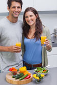 Zadowolona para trzymając szklankę soku pomarańczowego — Zdjęcie stockowe