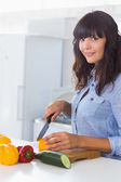 Pretty brunette chopping pepper — Stock Photo