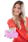 Blonde woman offering a present — Stock Photo