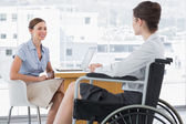 Businesswoman speaking with disabled colleague — Stock Photo