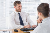 Businessman meeting with a co worker at his desk — Stock Photo