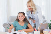 Smiling mother and daughter doing homework — Stock Photo