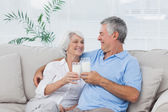 Couple clinking glasses of milk — Stock Photo