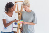 Friendly housemates choosing colour for wall — Stock Photo