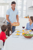 Man bringing a pizza to his family — Stock Photo