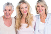 Three generations of cheerful women smiling at camera — Stock Photo