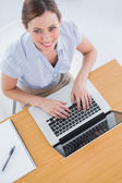 Businesswoman typing on her laptop and smiling up at camera — ストック写真
