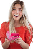 Surprised blonde woman opening gift — Stock Photo